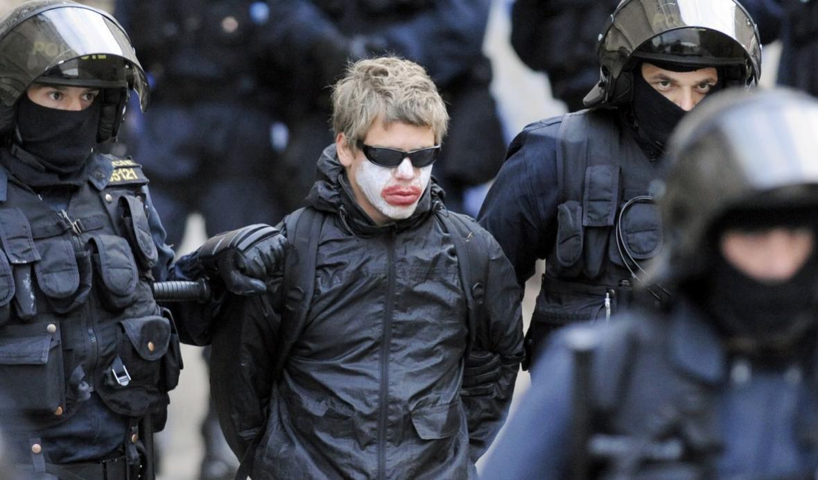 Policie odvádí zatčené squattery