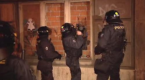 Policisté s beranidlem vnikají do domu