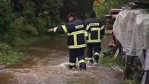 Hasiči se brodí v rozvodněné řece