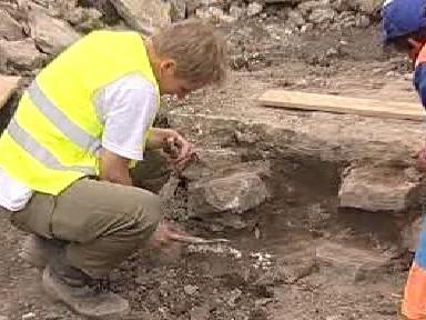 Archeolog odkrývá zbytky studny