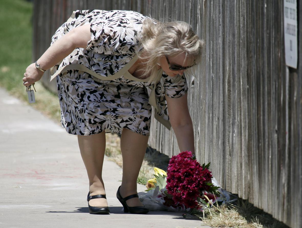 Žena kladoucí květiny k místu vraždy Dr. Tillera