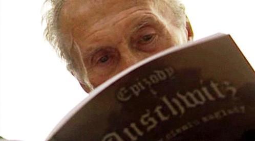 Bývalý osvětimský vězeň Kazimierz Smolen si čte komiks Láska ve stínu smrti