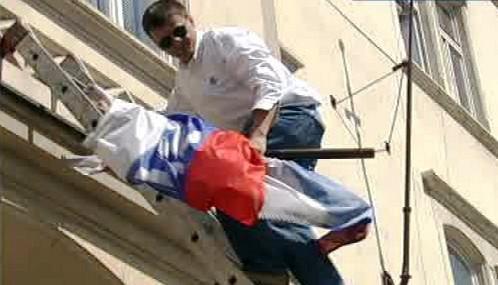 Slovenští aktivisté sundavají vlajku ze sídla SNS