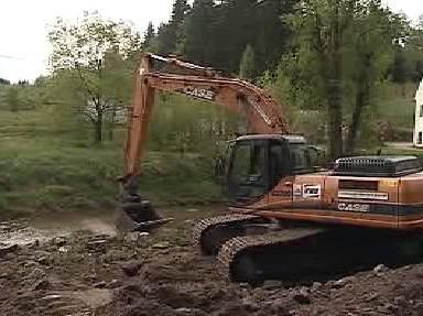 Bagr čistí koryto řeky od bahna