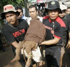 Záchranáři nesou oběť povodně