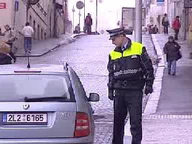 Strážník kontroluje zaparkované auto