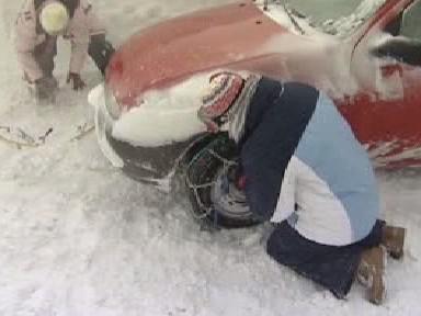 Řidič nasazuje řetezy na kola