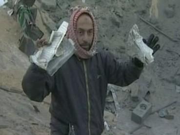 Palestinec vytahuje z trosek domu roztrhaný Korán