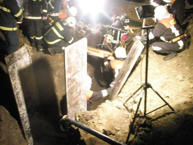 Záchranáři zpevňují stěny příkopu