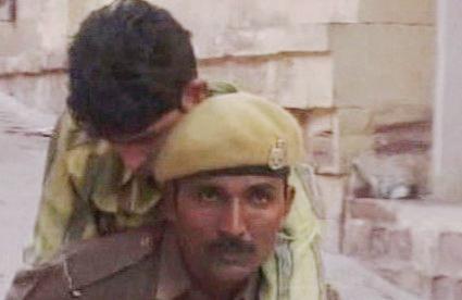 Indický policista pomáhá raněným