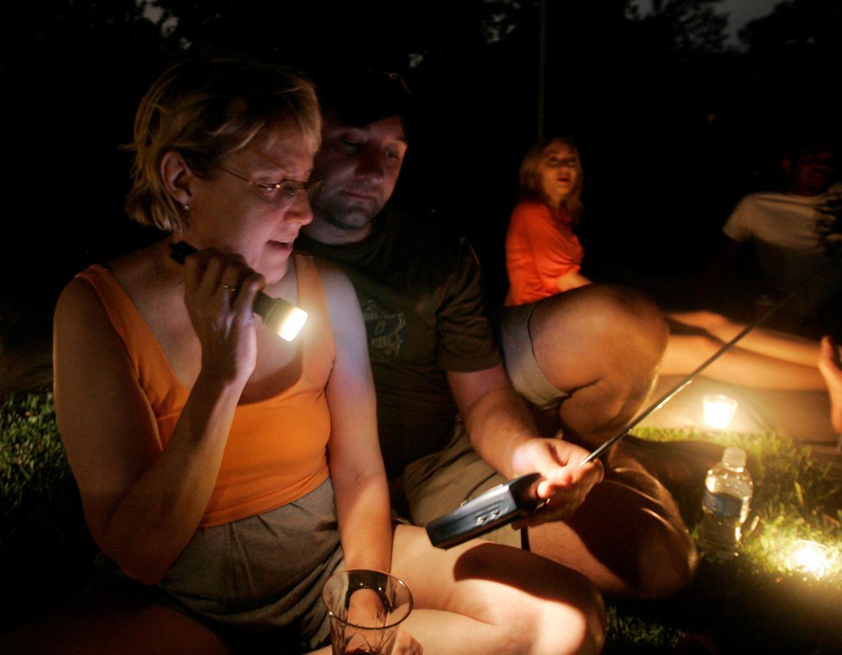 Obyvatelé Houstonu sledují zprávy na přenosné televizi