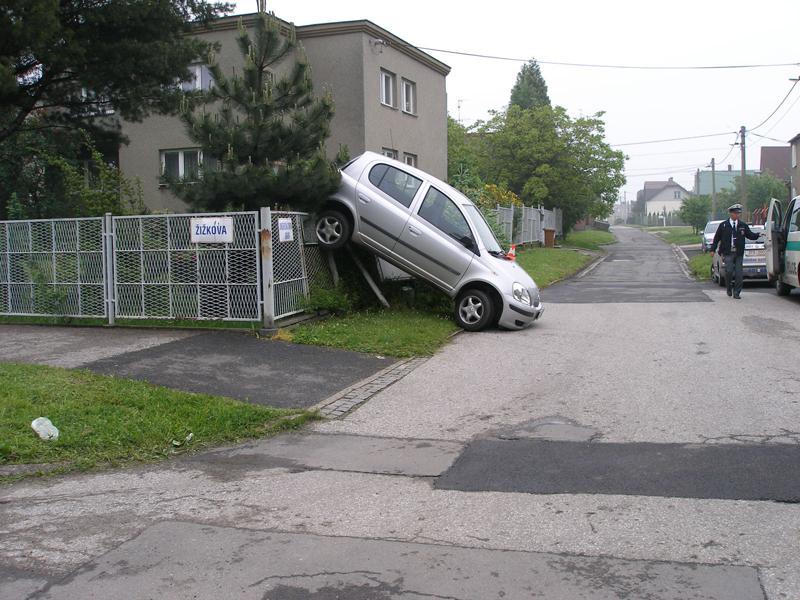 Toyota zaparkovaná na plotě