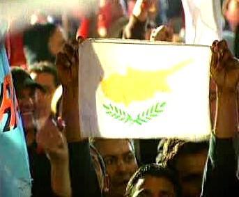 Kyperská vlajka v rukou demonstrantů.