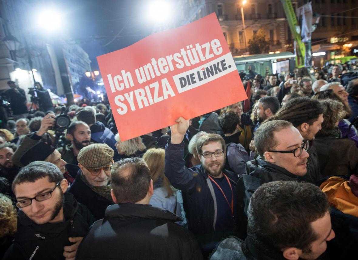 """""""Podporuji Syrizu,"""" hlásá plakát s logem německé levicové strany v rukou jednoho z příznivců řeckého hnutí Syriza."""