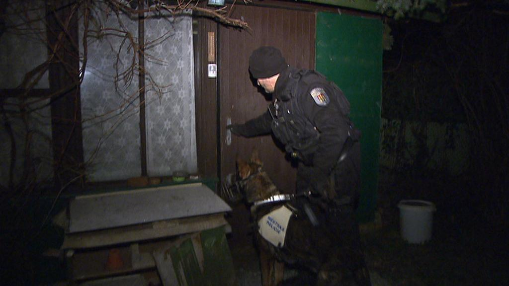 Policejní psovod kontroluje chatku