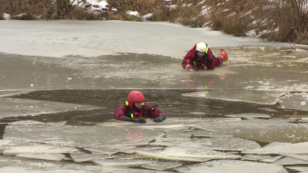 Jeden záchranář ve vodě, druhý se k němu snaží po ledu dostat