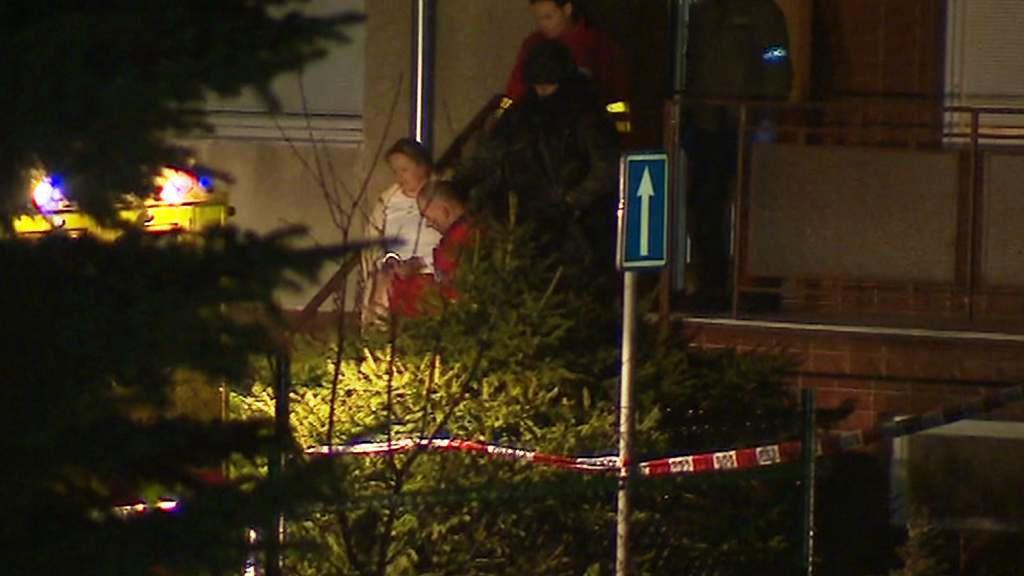 Záchranáři odvádí z bytu střelcovu manželku