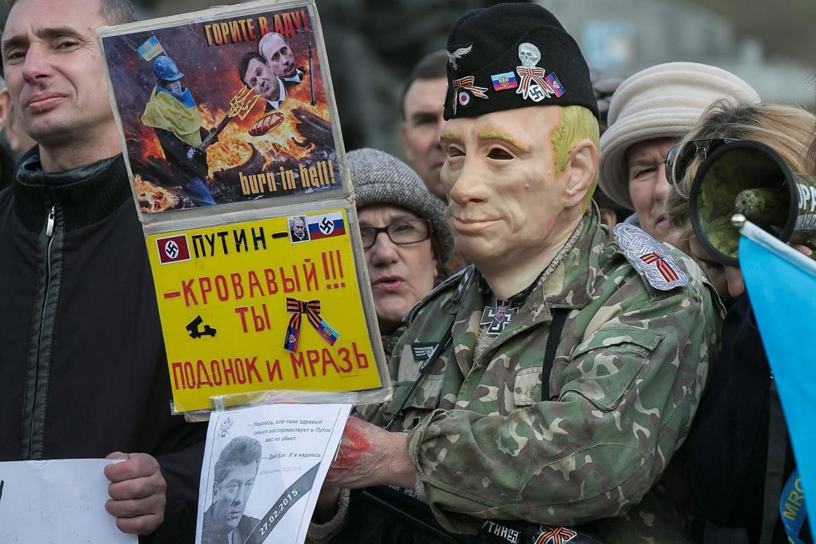 Jeden z účastníků pochodu v masce ruského prezidenta