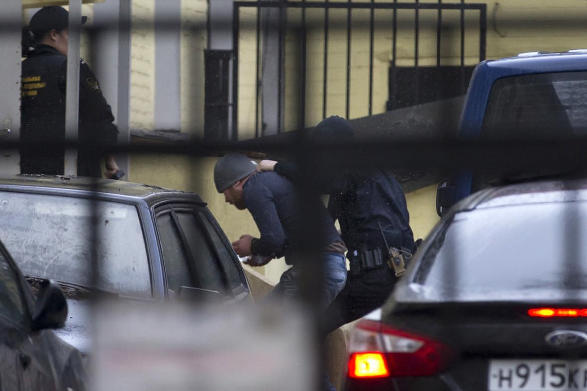 Ruská policie eskortuje jednoho z mužů zadržených v souvislosti s vraždou Borise Němcova