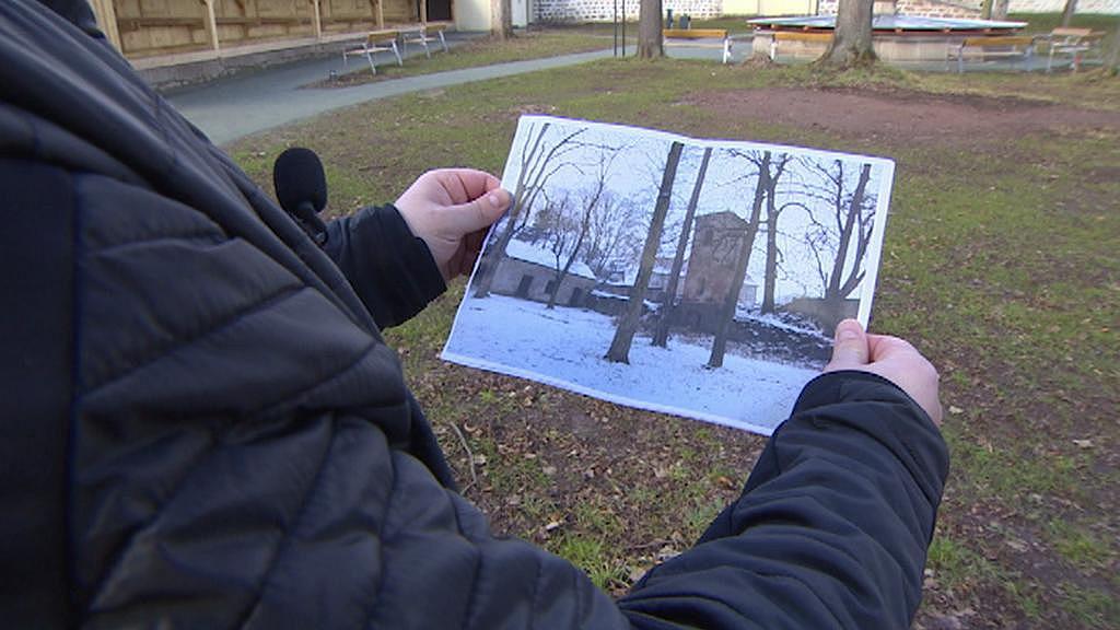 Správce broumovského kláštera ukazuje archivní fotografii klášterní zahrady
