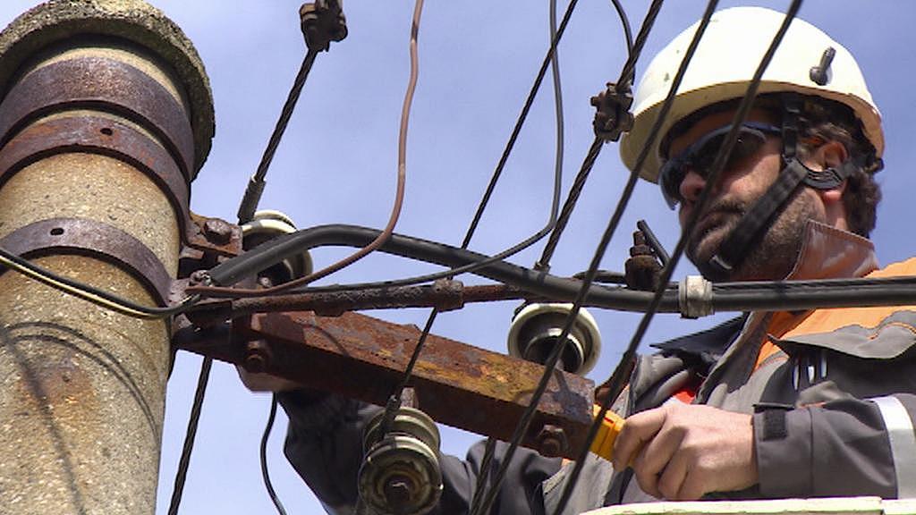 Montér firmy ČEZ opravuje elektrické vedení