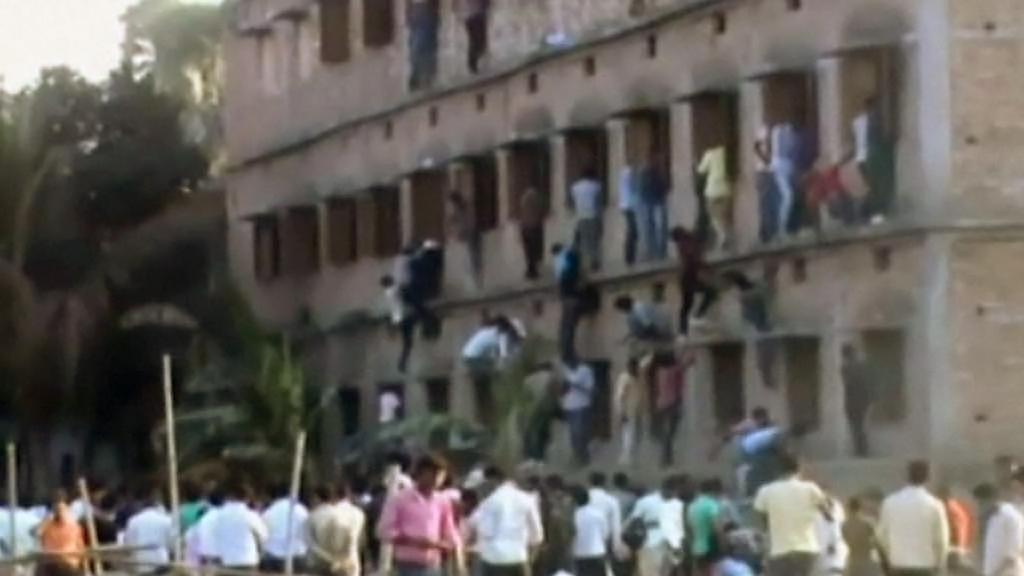 Příbuzní a kamarádi napovídají indickým studentům přímo do oken třídy