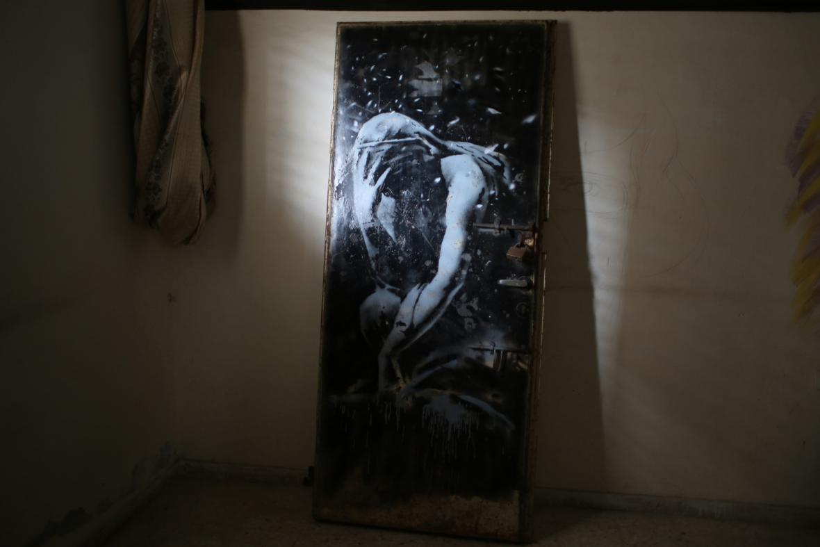 Banksyho plačící bohyně na železných dveřích