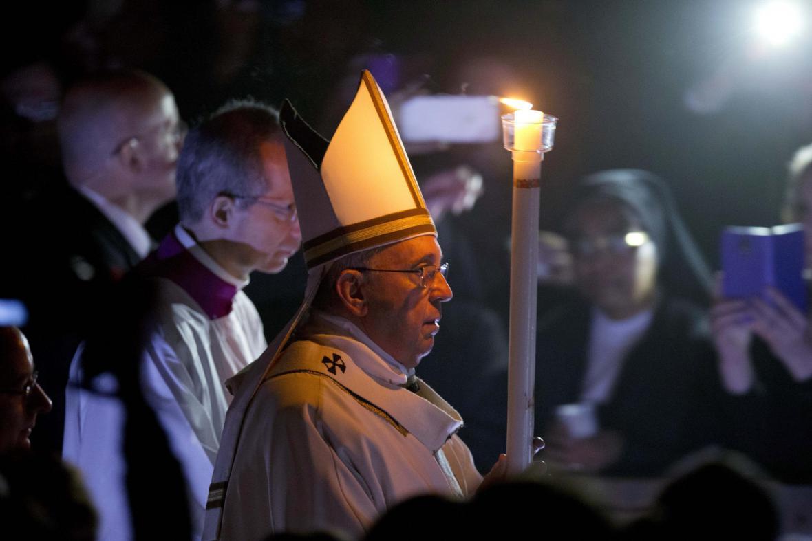 Papež František přichází s bílou svící na velikonoční vigilii