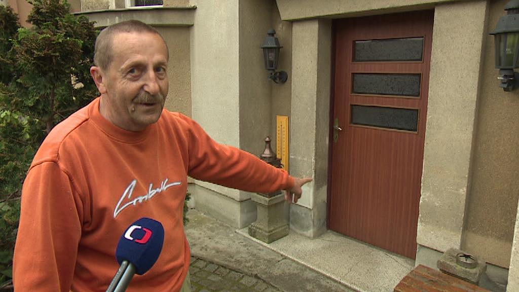 Jan Kovář ukazuje, kam až dosahovala voda při povodních