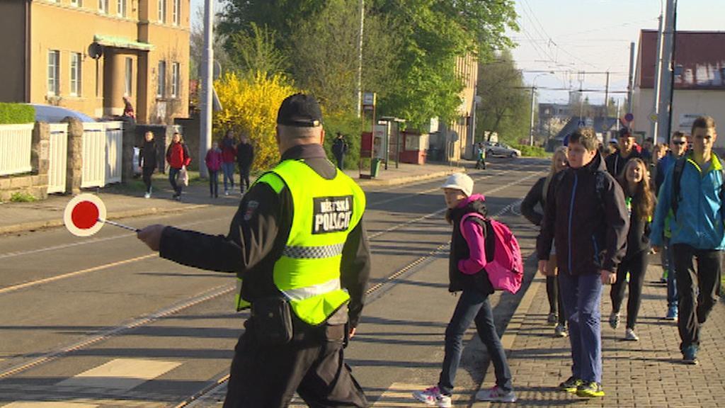 Strážník dohlíží na bezpečnost na přechodu