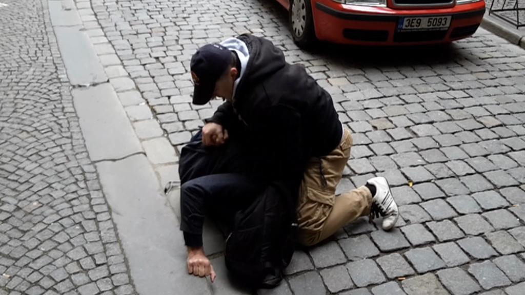 Policista zadržuje chodce, který šel na červenou