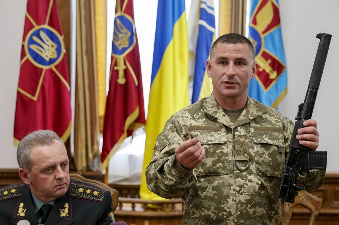 Ukrajinský důstojník ukazuje zbraň zabavenou zadrženým ruským vojákům
