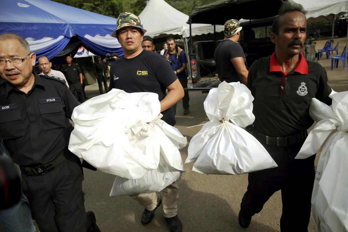 Malajsijská policie odváží těla z hrobů nalezených v džungli u hranic s Thajskem