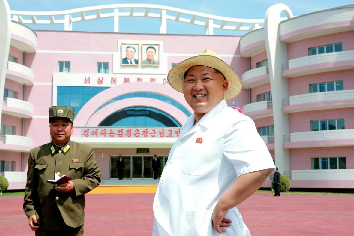 Kim Čong-un kouká na dětský domov ve Wonsanu vyzdobený obrázky jeho otce a děda