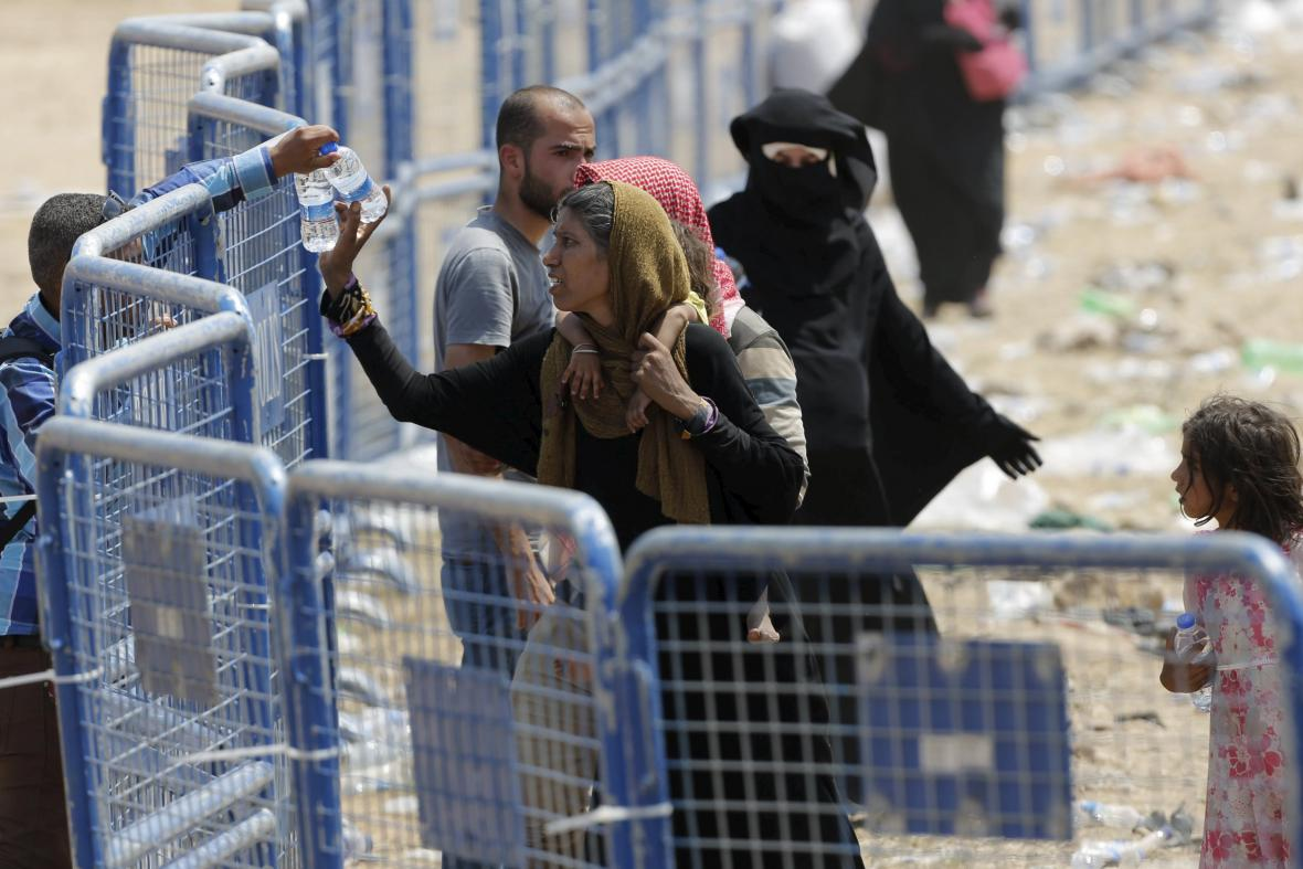 Syrská žena se svými dětmi čeká za bezpečnostními zátarasy po přechodu hranice do Turecka