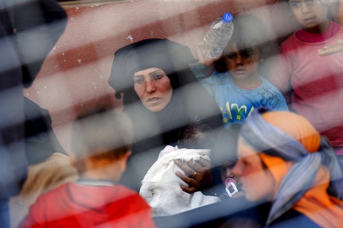 Syrská žena odpočívá po přechodu hranice to Turecka