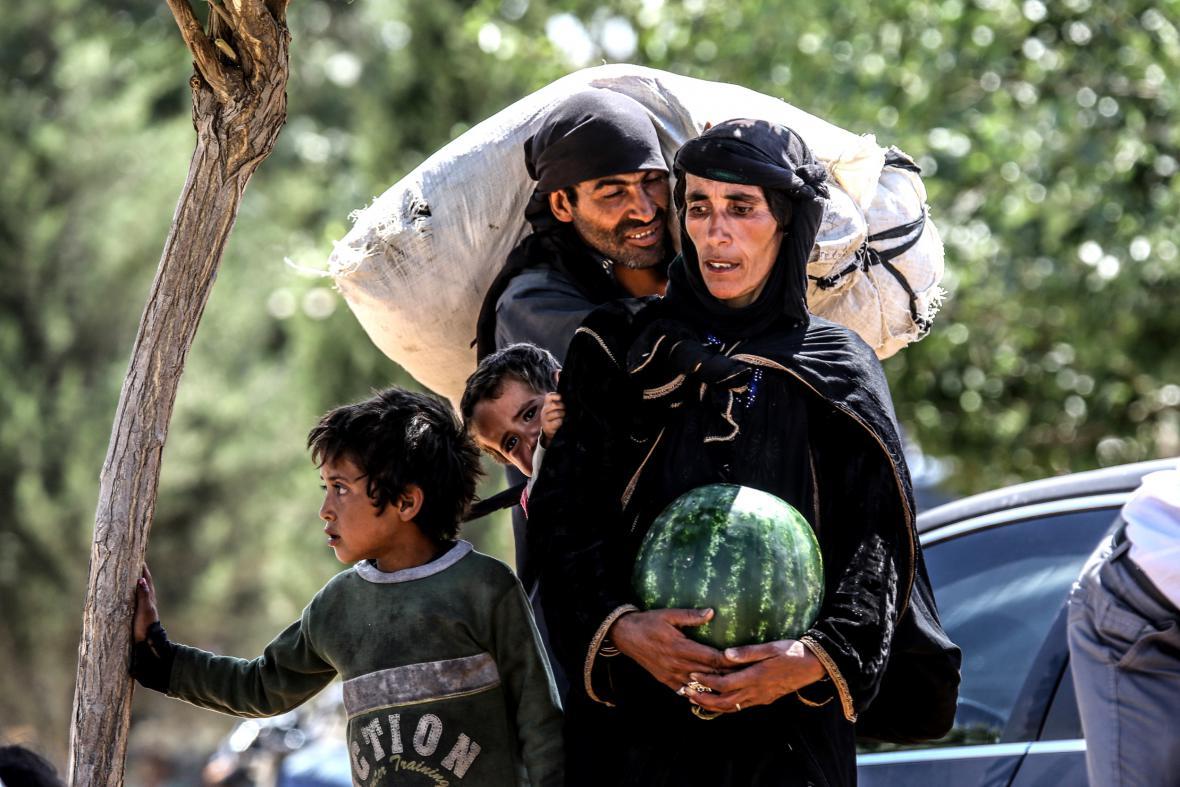 Syřané, kteří uprchli před boji mezi islamisty a Kurdy, si odnášejí melouny, které jim rozdali obyvatelé Turecka