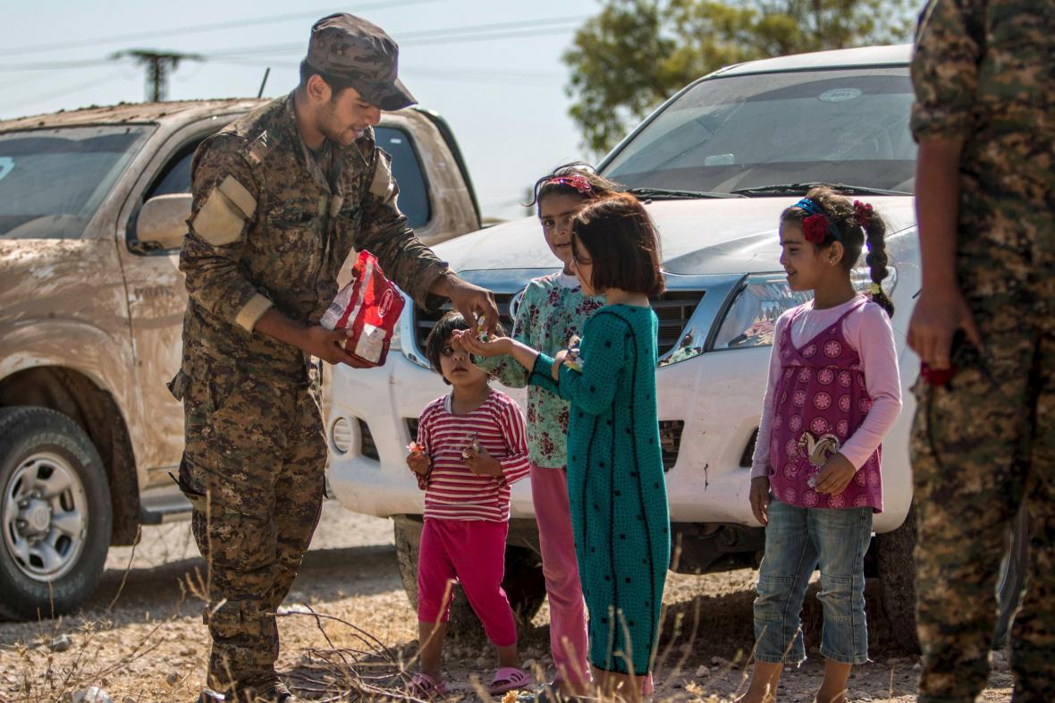 Příslušník kurdské milice rozdává sladkosti dětem v Tall Abjadu