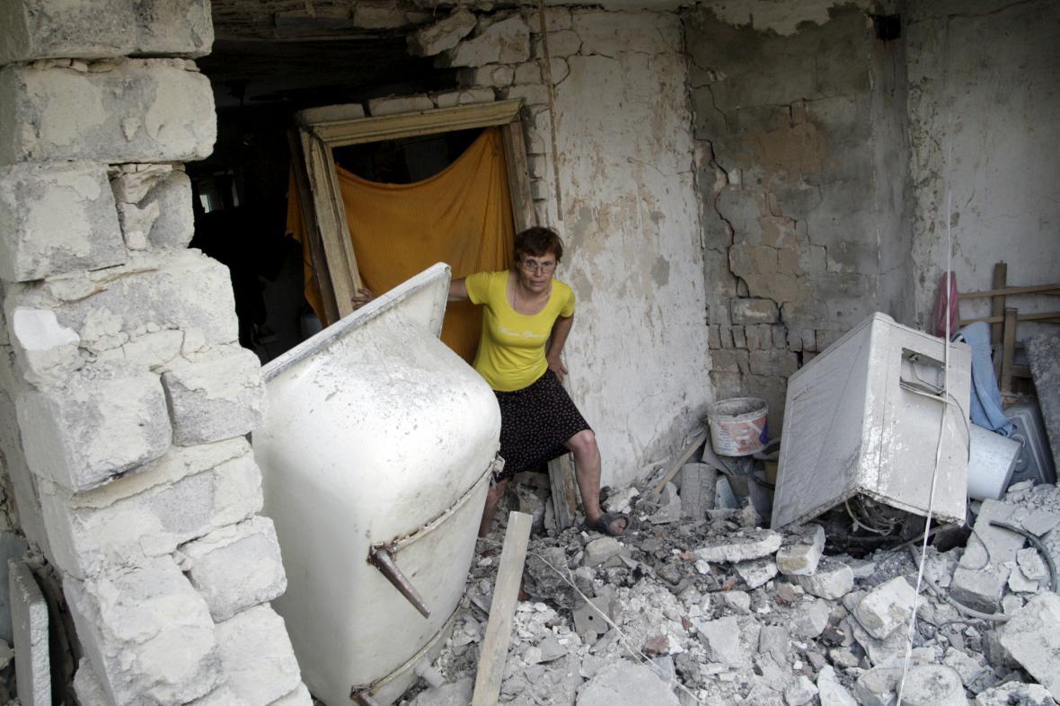 Obyvatelka Doněcku prohlíží trosky svého domu
