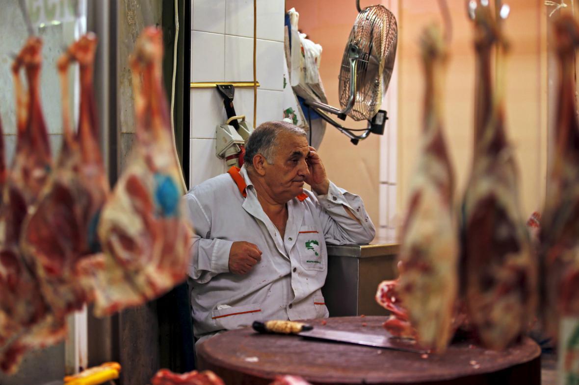 Řezník čeká ve svém obchodě na zákazníky