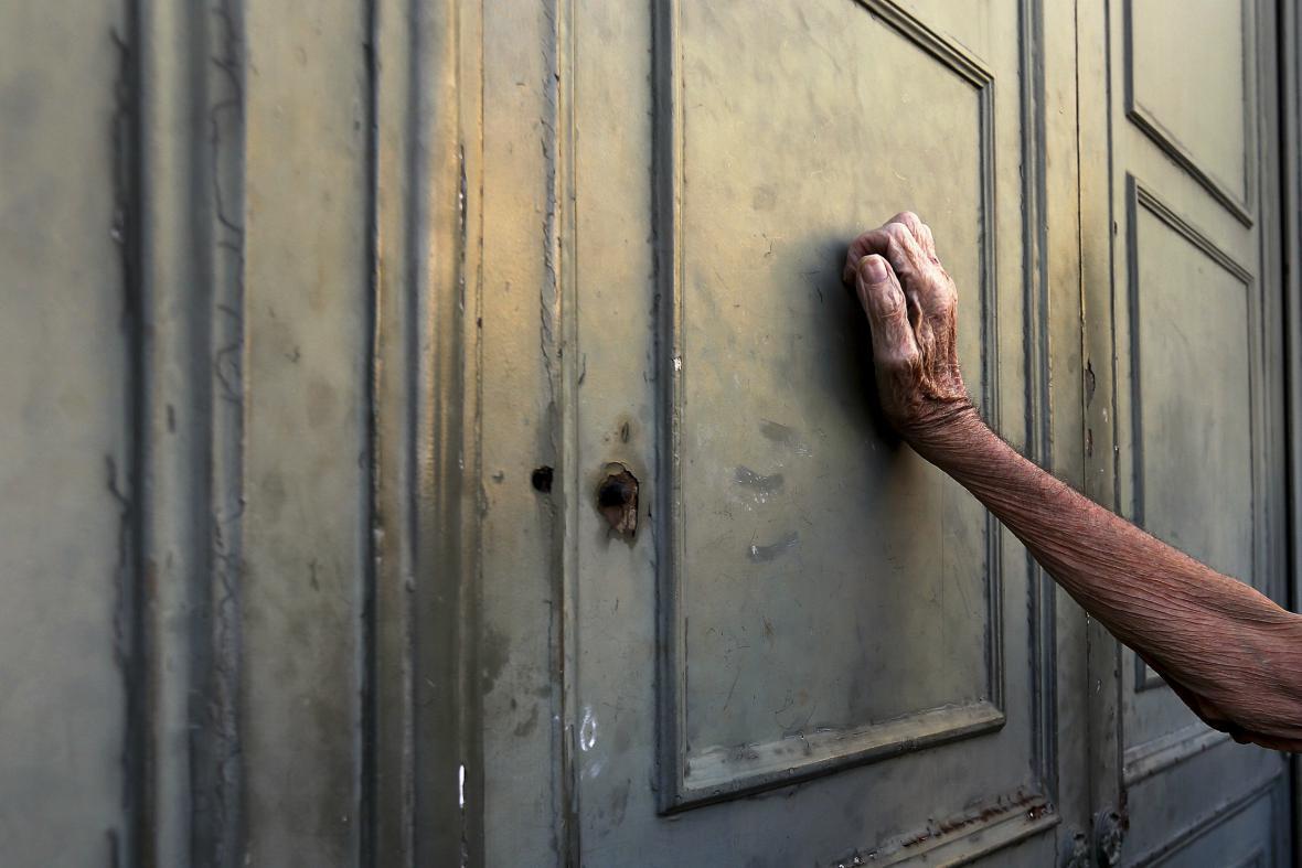 Řecký důchodce před pobočkou Národní banky žádá vyplacení části své penze
