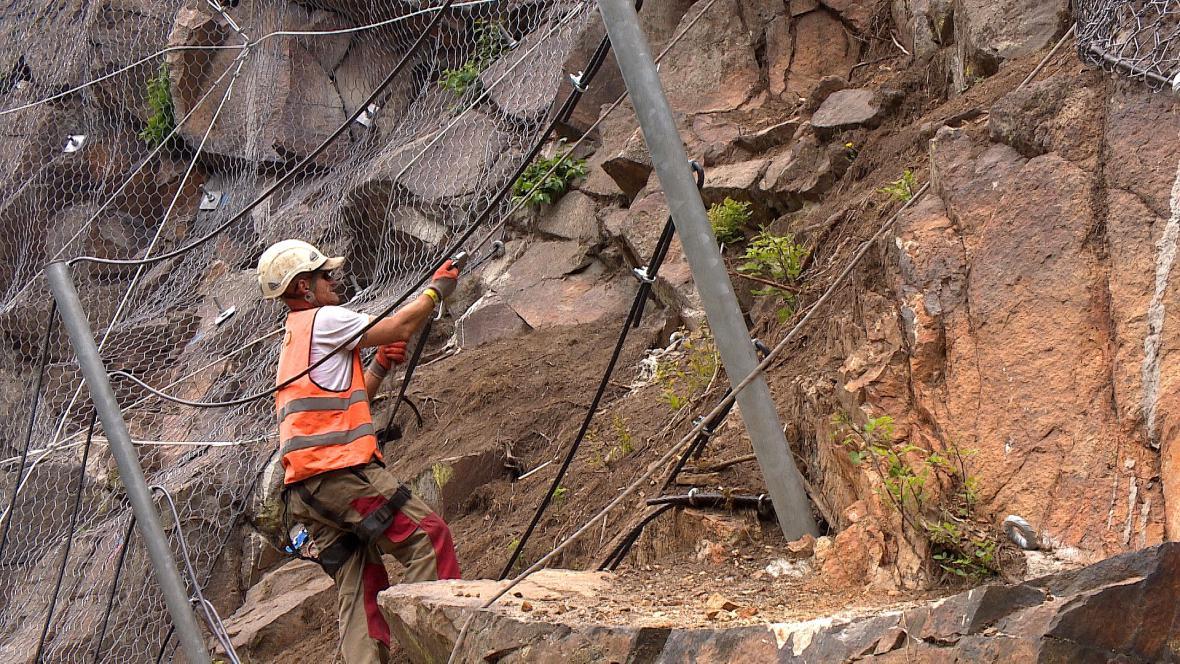 Dělníci pracují zajištění jako horolezci