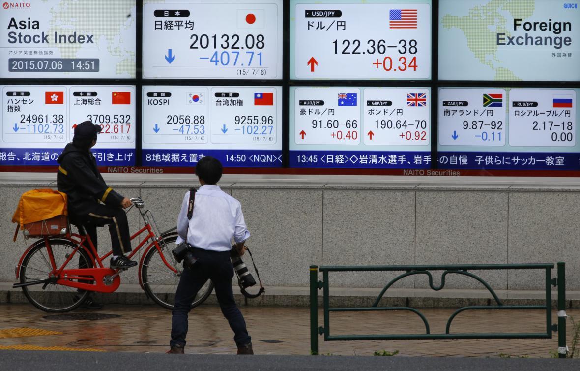 Lidé v Tokiu sledují vývoj akciových indexů, které po řeckém referendu zaznamenaly pokles