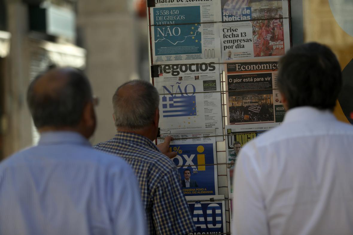 Portugalci si čtou titulní strany novin, které informují o výsledku řeckého referenda