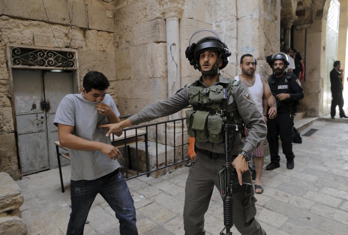 Izraelský policista brání palestinskému mladíkovi ve vstupu do Starého města