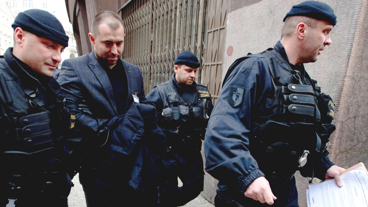Advokát Ivo Hala v doprovodu policistů