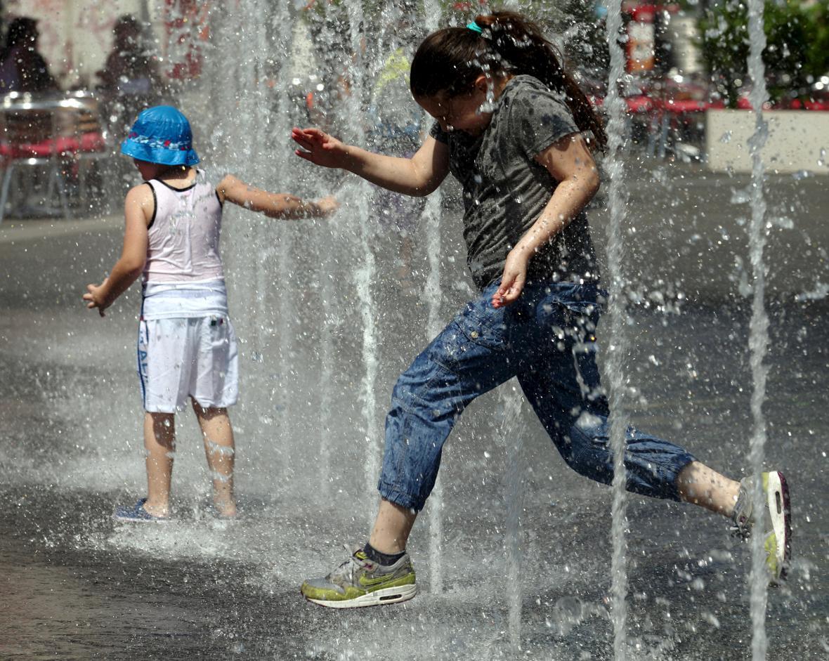 Děti se chladí uvnitř jedné z vídeňských fontán