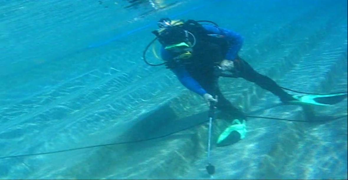 Potápěč opravuje dno bazénu