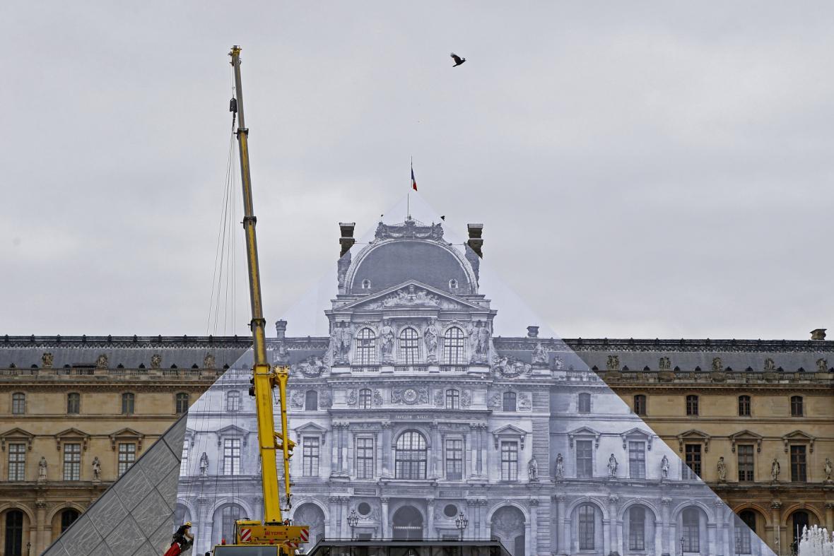 Počin umělce JR na pařížské galerii Louvre