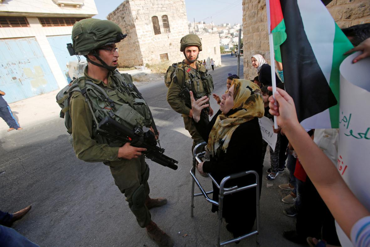 Izraelští vojáci hovoří v Hebronu s palestinskou ženou